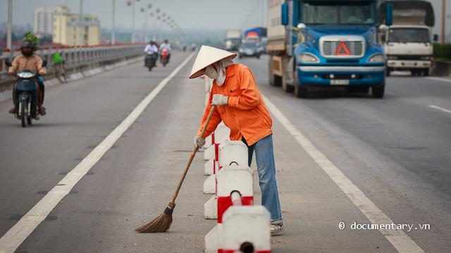 Một công nhân đang quét dọn trên mặt cầu Thanh Trì - Hà Nội, chiều 24/8/2012. Cầu Thanh Trì dài 3km, chia làm hai chiều riêng biệt. Một công nhân khác cho biết mỗi ngày chị phải làm việc 8 tiếng, tiền công là 100.000đ/ngày.