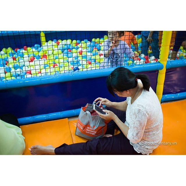 [Instagram] A #woman plays #game on her #smartphone in a #playground for #kids. #Hanoi, #November 2015.